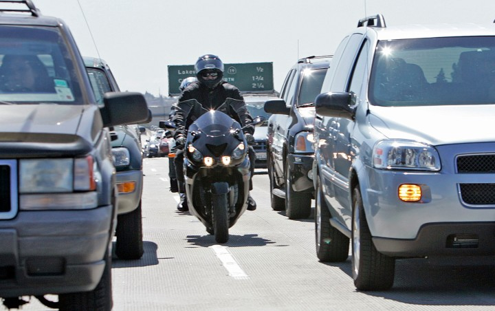 """Shepler, Lori –– – 125933.ME.0711.LANESPLIT3.ls.jpg –––––– Shear""""Ree,(front) head of Southern California Sport Bike Association, and Mark Russell,17, go between cars on the southbound 405 in Long Beach on July 10, 2007."""